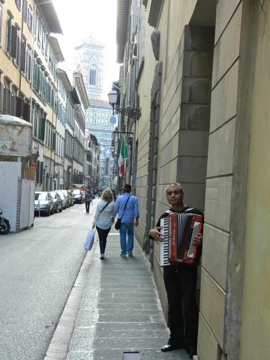 Nestled into a doorway, an accordion player sings for his supper.
