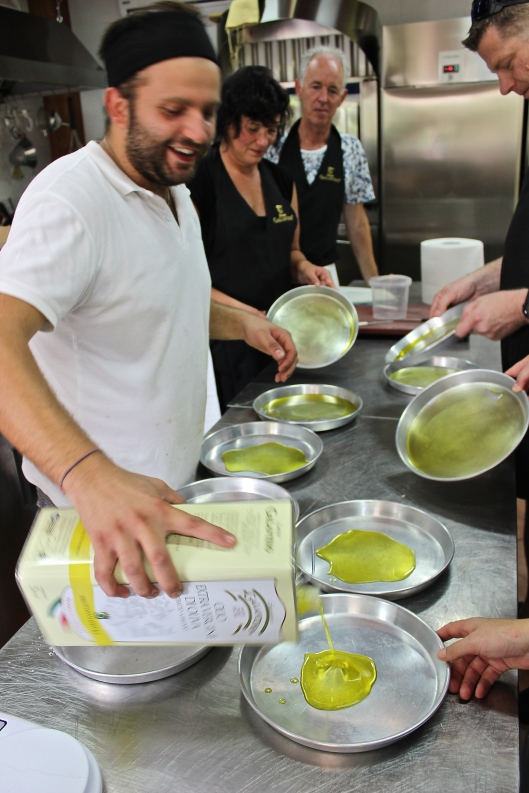 Significant amounts of olive oil coat the foccacia pans. All this oil enhances the flavor of this delicious Italian staple.